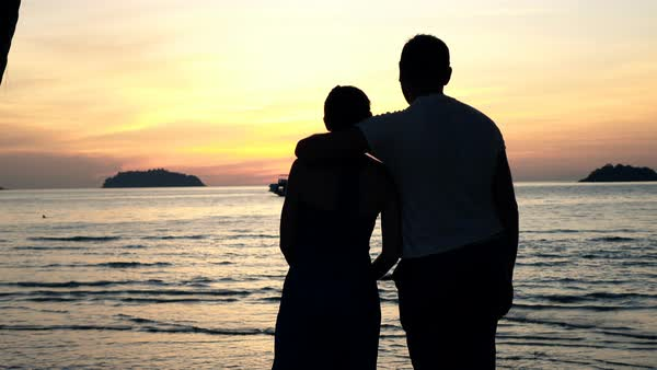Silhouette of couple hugging and admire sunset on beach - Stock Video  Footage - Dissolve