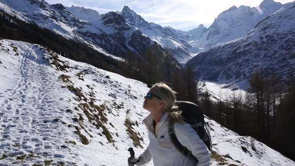Woman hikes up snowy mountain trail, looks out to view Royalty-free stock video