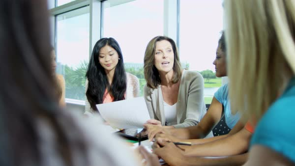 Young multi ethnic female students sitting around table with Caucasian American female college lecturer  Royalty-free stock video