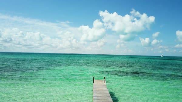 Scenic view of jetty on tranquil tropical Caribbean beach at an idyllic  luxury summer vacation resort  Ocean with blue water on a sunny day,  Bahamas