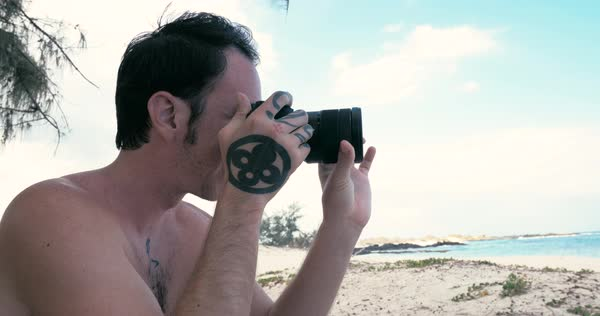 Close-up shot of a man taking pictures on a beach Royalty-free stock video