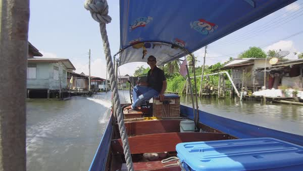 BANGKOK, THAILAND - MARCH 2017, LOW ANGLE: Focused Thai male sitting in the  back of a cool boat piloting the vessel  Asian tour guide steering tourist