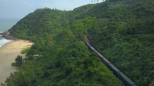 Long freight train crossing the lush tropical island enters a dark tunnel   stock footage