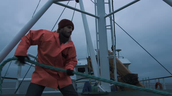 Serious seaman pulls the thick rope during traveling on the ship Royalty-free stock video