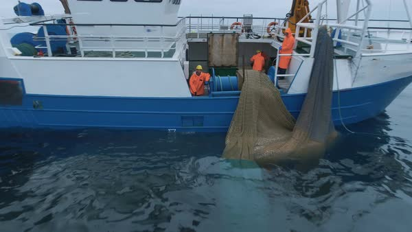 Zoom out of a commercial ship fishing with trawl net on the sea. Royalty-free stock video