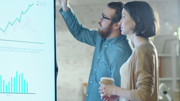 Young man and woman discuss charts drawn on their electronic whiteboard. man shows details on the screen woman listens holding cup of coffee in her hands.their office is developer and modern looking. Royalty-free stock video