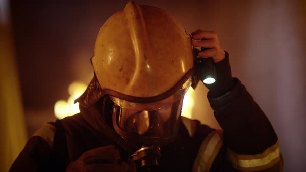 Tired firefighter takes off his helmet inside a burning building Royalty-free stock video
