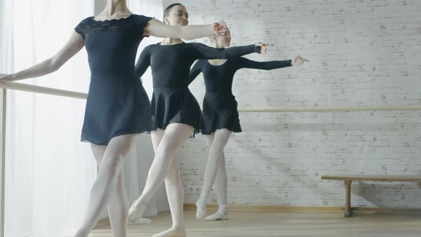 Three young and beautiful ballerinas doing stretches at the barre in the morning Royalty-free stock video