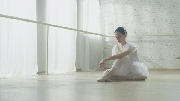 Young beautiful ballet dancer sitting on the wooden floor in her tutu dress and tying her pointe shoes Royalty-free stock video