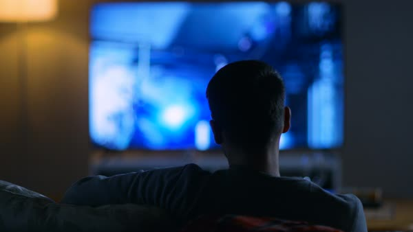 Back view of a man sitting on a couch watching movie on his big flat screen tv Royalty-free stock video