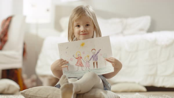 Cute young girl sitting on pillows shows drawing of her family. Royalty-free stock video