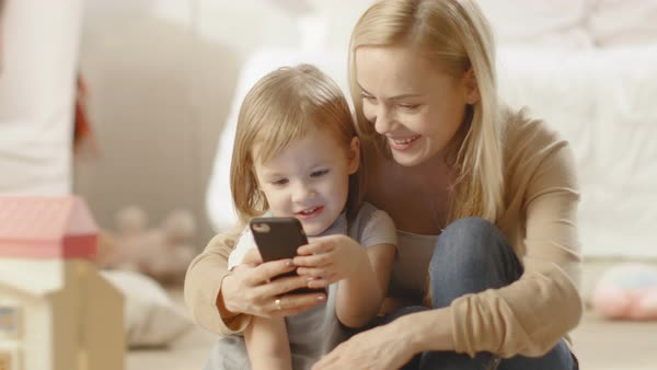 Beautiful young mother sits with her little daugher and shows her something interesting on a smartphone. Children's room is full of toys. Royalty-free stock video