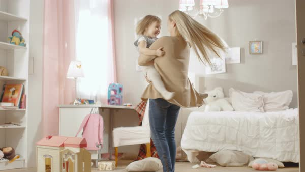 Young sweet mother holds her little cute daughter in arms and spins with her. Children's room is pink and full of toys. Slow motion. Royalty-free stock video