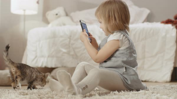 Cute little girl sits on the floor with smartphone and shoots video of her striped kitten walking around. Slow motion. Royalty-free stock video