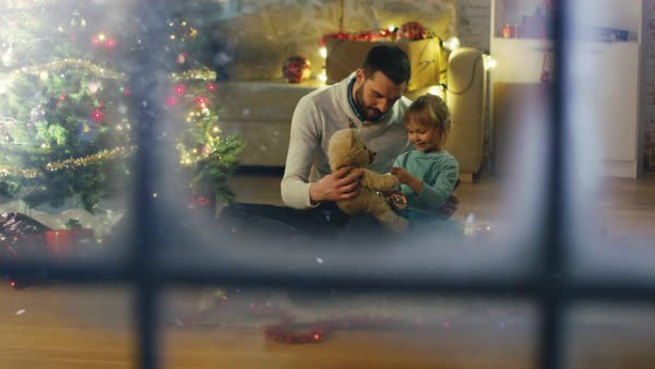 Looking Through Snowy Window. Sitting Under Christmas Tree Father and Daughter Play with Plush Bear. Royalty-free stock video
