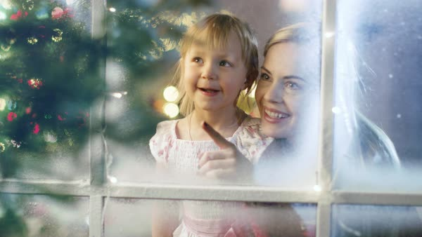 On Christmas Eve Mother and Daughter Looking Through Snowy Window. Garland Shines Bright on a Window. Royalty-free stock video