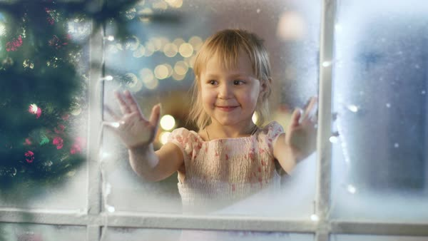 On Christmas Eve Cute Little Girl Looks Through the Window and Smiles. Royalty-free stock video