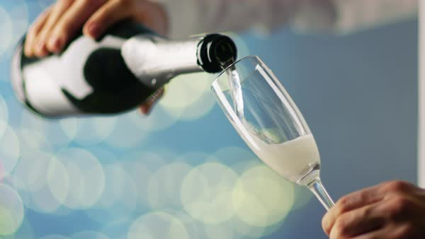 Man Wearing White Shirt Pouring Champagne into Champagne Glass. Background is Blue with Blurred Lights Shining. Royalty-free stock video