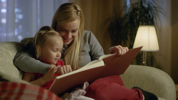 Mother and her cute daughter are sitting on a couch in the living room. They're reading children's book. It's evening. Royalty-free stock video