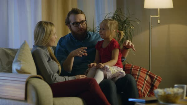 In the evening family spends time together sitting on a couch in a living room. Little girl sits on her father's laps and parents tickle her. Royalty-free stock video