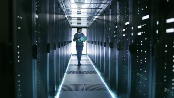 Male server engineer walks with laptop through working data center full of rack servers. Royalty-free stock video