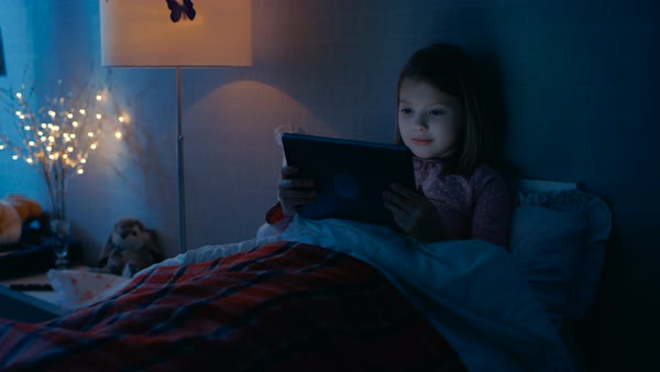 Cute little girl in her bedroom lies in bed with tablet computer. Royalty-free stock video