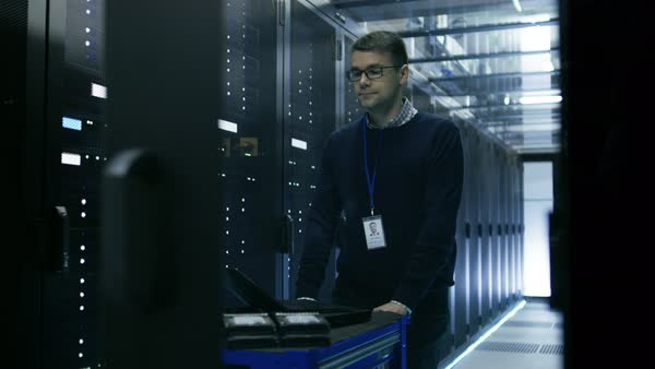 IT technician in data center pushes crash cart through sliding doors. Rows of working rack servers are visible. Royalty-free stock video