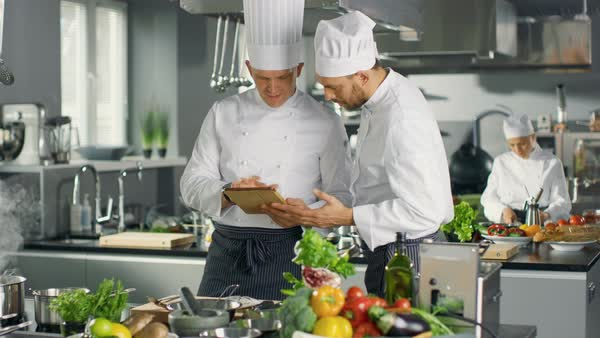 Two Chefs Discuss while Using Tablet Computer. They Work in Big Restaurant Stainless Steel Professional Kitchen. Royalty-free stock video