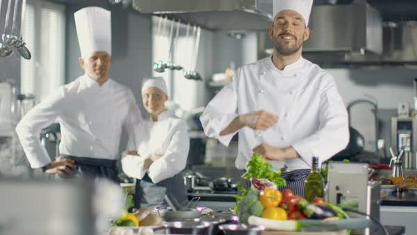 Chef of a Big Restaurant Crosses Arms and Smiles in a Modern Kitchen. His Staff in Smiling in the Background. Royalty-free stock video