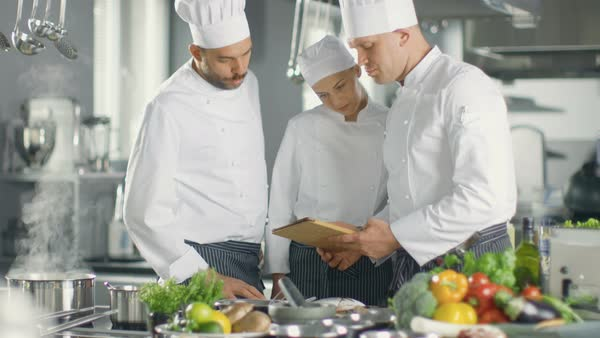 In the Modern Kitchen Team of Cooks Use Tablet Computer For Recipes, They Smile and Have Discussion. Kitchen is Full of Food Ingredients, Vegetables, Meat, Boiling Soup. Royalty-free stock video