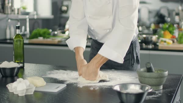 Baker Chef Kneads the Dough in a Modern Looking Kitchen. Royalty-free stock video