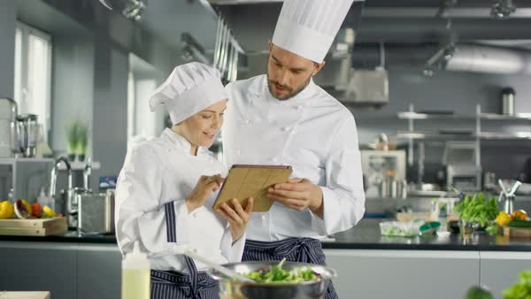 Male and Female Chefs Discuss while Using Tablet Computer. They Work on a Big Restaurant Stainless Steel Professional Kitchen. Royalty-free stock video