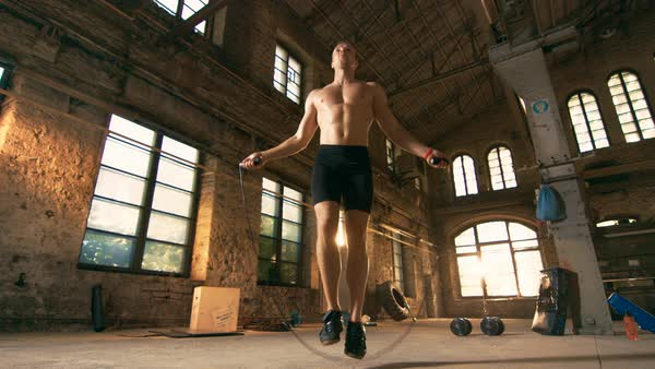 Athletic shirtless fit man exercises with jump  skipping rope in a deserted factory hardcore gym Royalty-free stock video