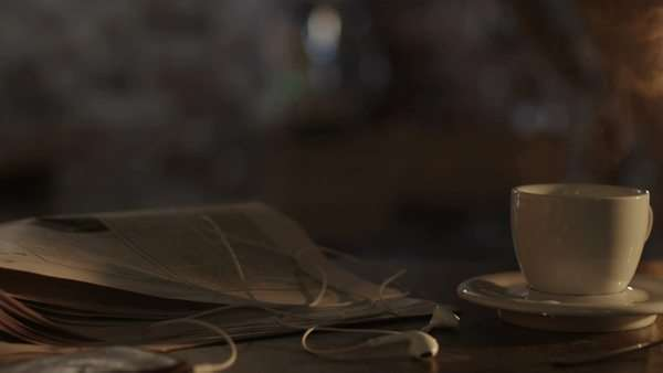 Shot of coffee cup and newspaper on table in morning sunlight. Royalty-free stock video