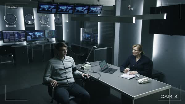 Female special agent conducts lie detector test on a young suspect stock  footage
