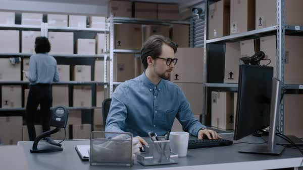 Warehouse inventory manager works on a computer while sitting at his desk,  in the background, female worker uses digital tablet computer to check