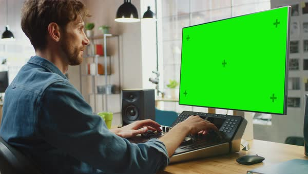 Male video editor using an editing console deck to color-grade footage on  his computer with green screen in loft office stock footage