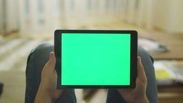 Man is laying on couch at home and holding tablet with green screen in landscape mode on lap Royalty-free stock video
