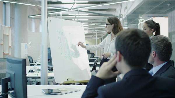 Team of office workers have meeting. Woman does presentation with graphs on whiteboard. Royalty-free stock video