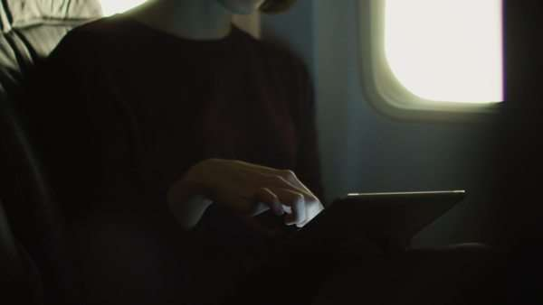 Young woman in close-up is using a tablet inside an airplane next to a window. Royalty-free stock video