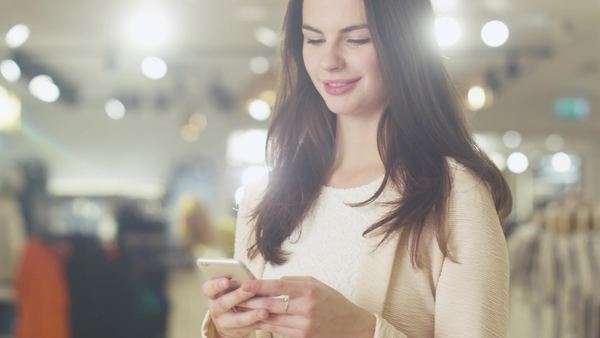 Happy young brunette girl is standing in a department store and using a smartphone. Royalty-free stock video
