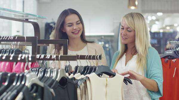 0ab8e92f596 Two happy young girls are shopping clothes in a department store. By  Gorodenkoff. Stock Footage ...