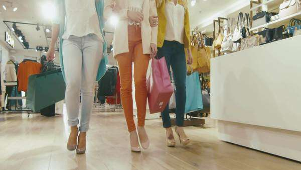 Low shot of female legs walking towards the camera through a department store in colorful garments with shopping bags. Royalty-free stock video