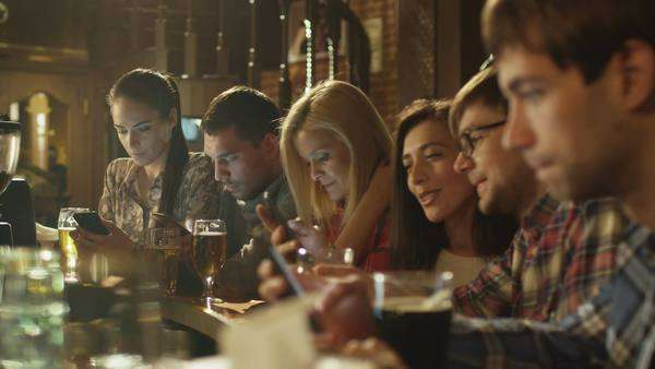 Friends laugh, use smartphones while having a good time together at a bar. Royalty-free stock video