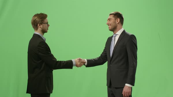 Two businessmen in suits are having an agreement with a handshake on a mock-up green screen in the background. Royalty-free stock video
