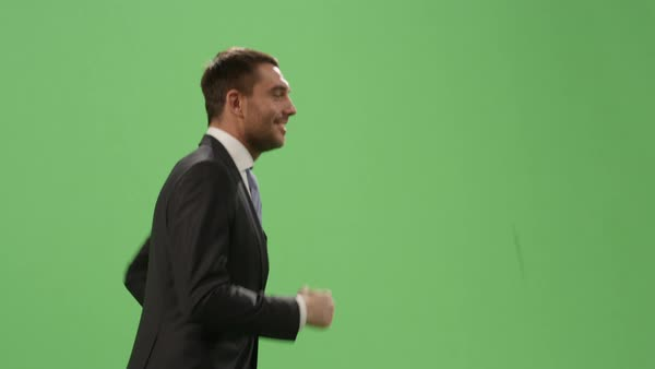 Happy businessman in a suit is running on a mock-up green screen in the background. Royalty-free stock video