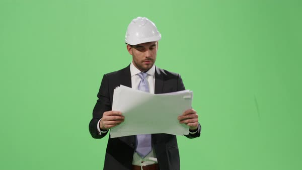 Businessman in a hard hat and a suit is walking and looking at paper documents on a mock-up green screen in the background. Royalty-free stock video