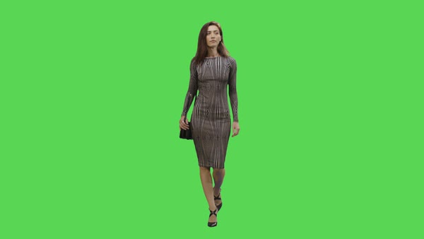 Casual young brunette girl in a dress is walking on a mock-up green screen in the background. Royalty-free stock video