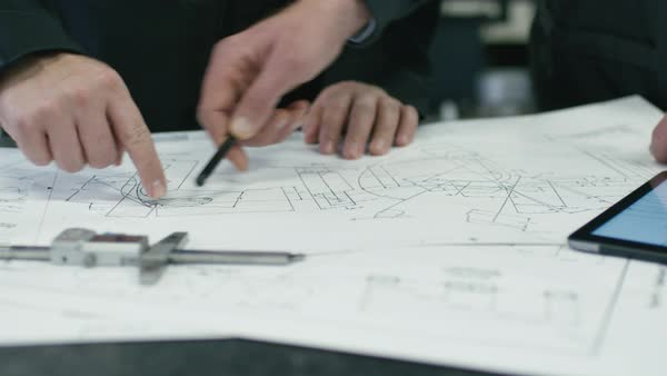 Close-up of two engineers discussing a blueprint in a factory. Royalty-free stock video