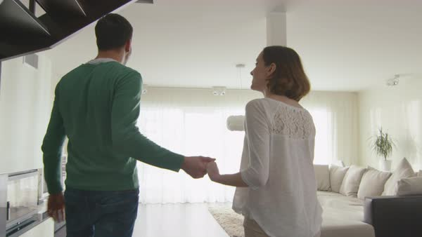 Happy couple are walking into a new home and looking around the apartment. Royalty-free stock video
